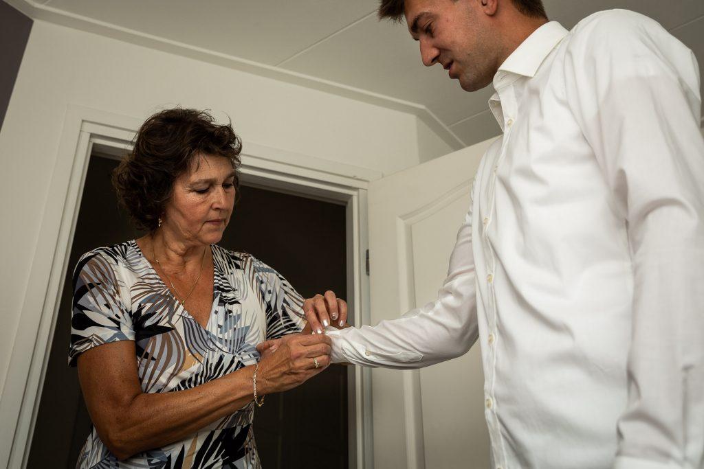 Bruidsfotografie Noord Holland klaarmaken bruidegom in het huis van zijn ouders waarbij zijn moeder helpt met de manchetknoop