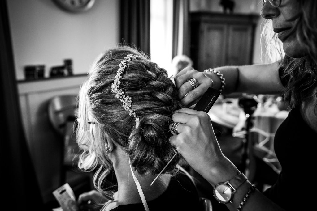 Kapper vlecht het haar in van de bruid en zet het bruidssieraad vast in haar haar
