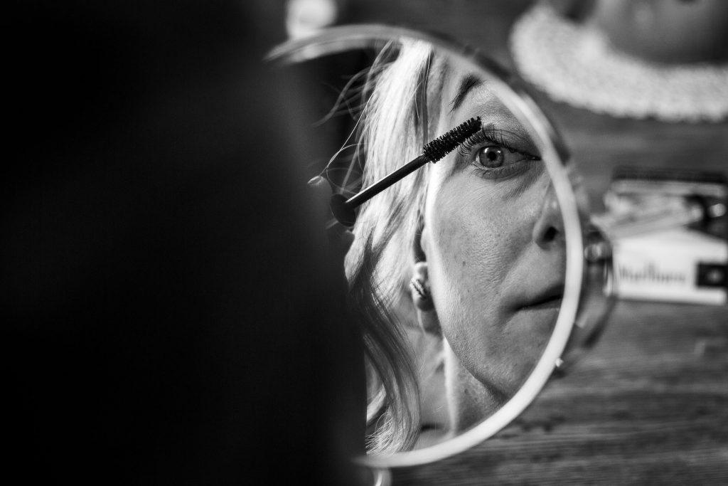 Bruid doet haar eigen make-up en brengt mascara aan eigen bruidsvisagie