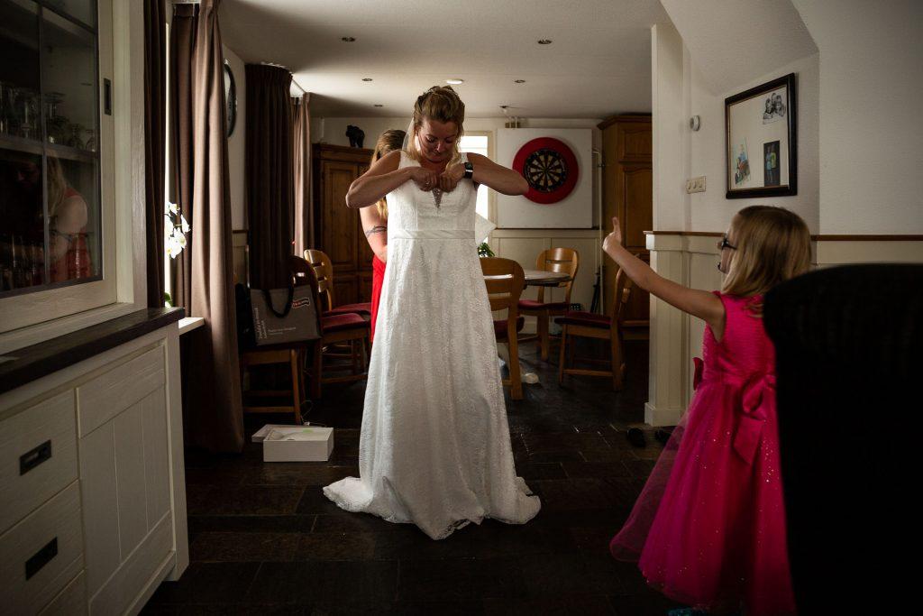 Bruidsmeisje keurt de trouwjurk goed van de bruid. Haar zus ritst de jurk dicht