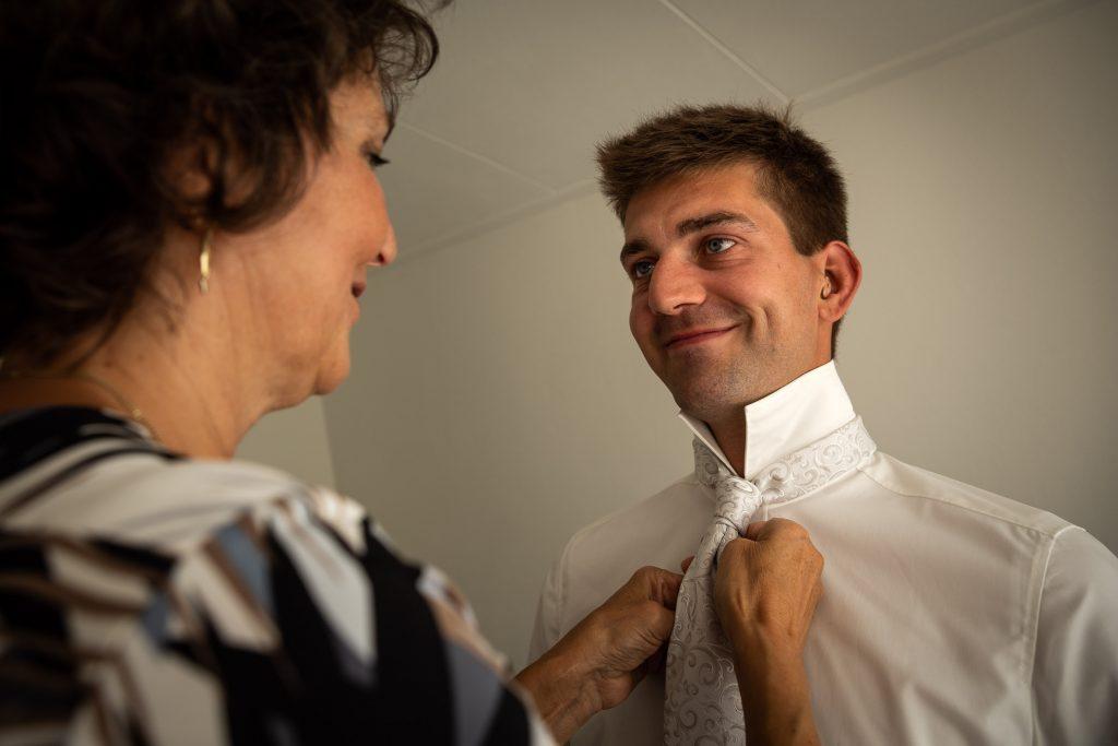 De bruidegom maakt zich klaar voor de trouwdag in zijn ouderlijk huis. Zijn moeder strikt zijn stropdas
