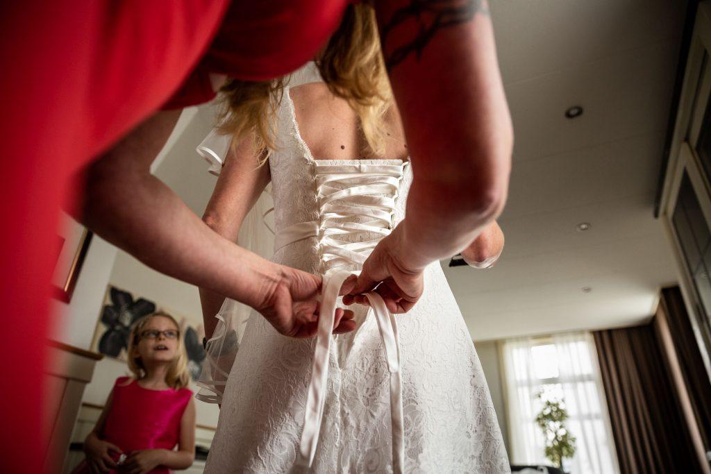 Zus van de bruid is bezig met het inrijgen van de veter in de bruidsjurk onder toeziend oog van het bruidsmeisje