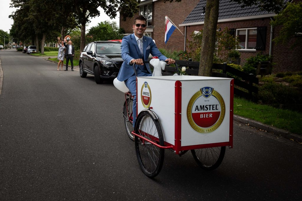 Bruidegom fietst vanaf zijn ouderlijk huis met de bakfiets naar zijn bruid hij wordt uitgezwaaid door zijn ouders