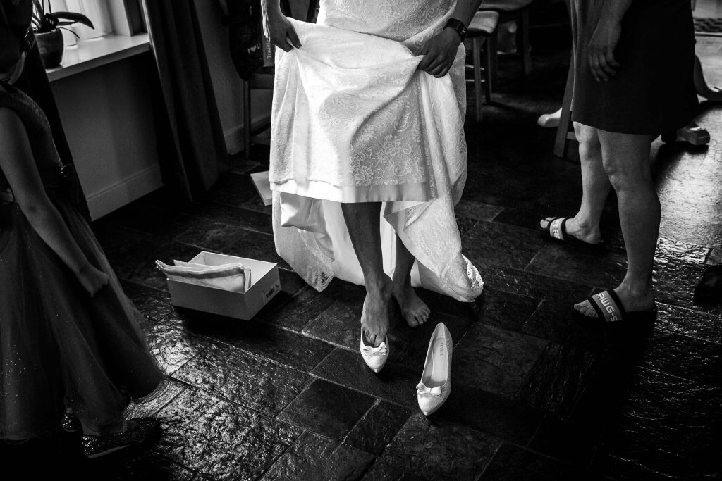 Getting ready van de bruid aantrekken van de witte trouwschoenen