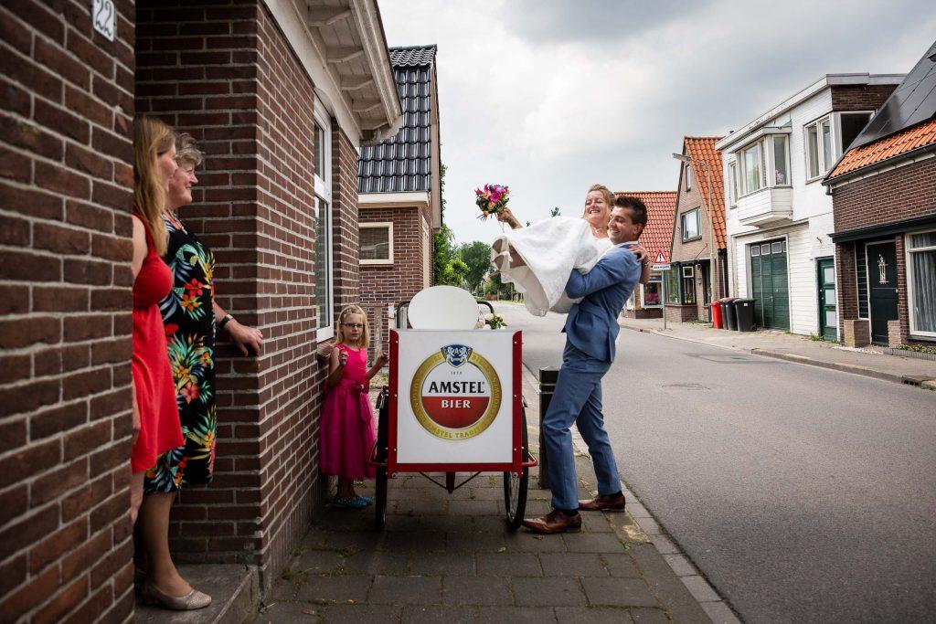 Bruidegom tilt zijn bruid in de Amstel bakfiets op hun trouwdag bij haar ouderlijk huis in spanbroek
