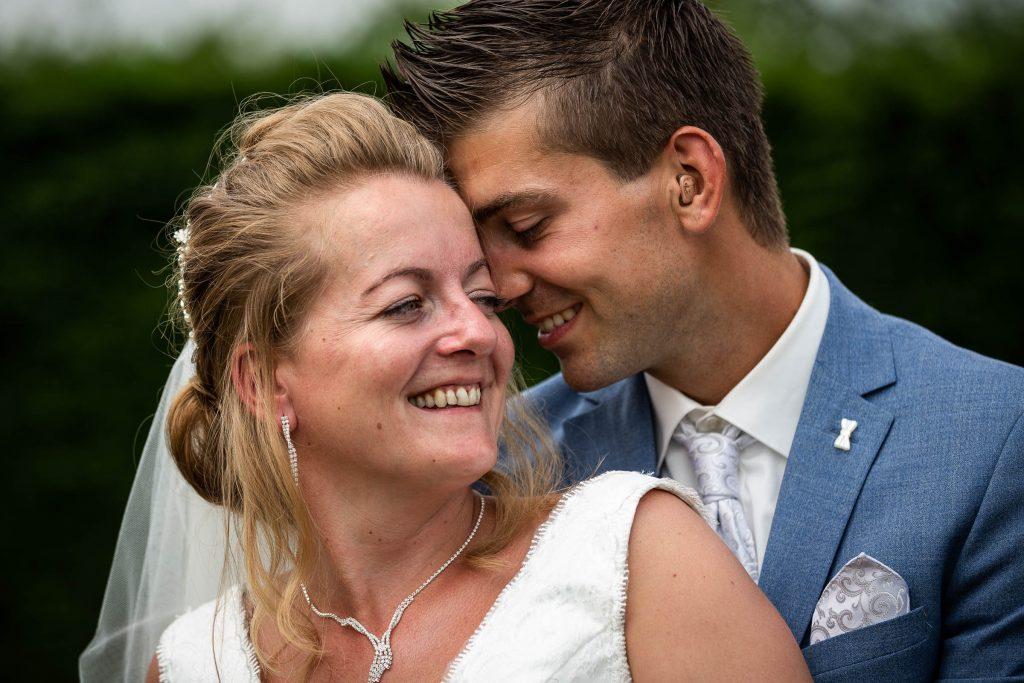 Liefdevol bruidspaar die samen knuffelen op hun trouwdag in spanbroek