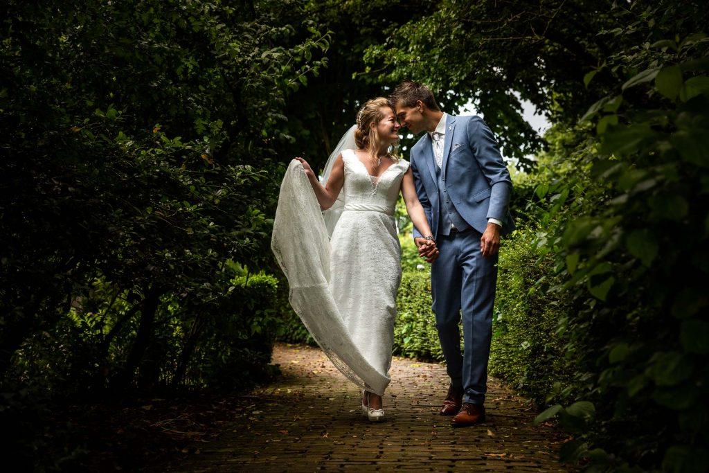 Bruidspaar loopt samen verliefd hand in hand tussen het groen van een mooi park in noord Holland tijdens hun bruiloft