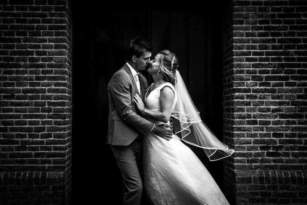 Trouwfoto van een mooi liefdevol bruidspaar waarbij de sluier net een beetje wind vangt voor de kerk in spanbroek waar zij trouwen