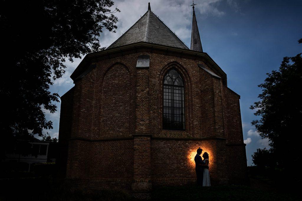 Een creatieve trouwfoto van een bruidspaar voor 't kerkhuis in spanbroek, de kerk waar zij zullen trouwen