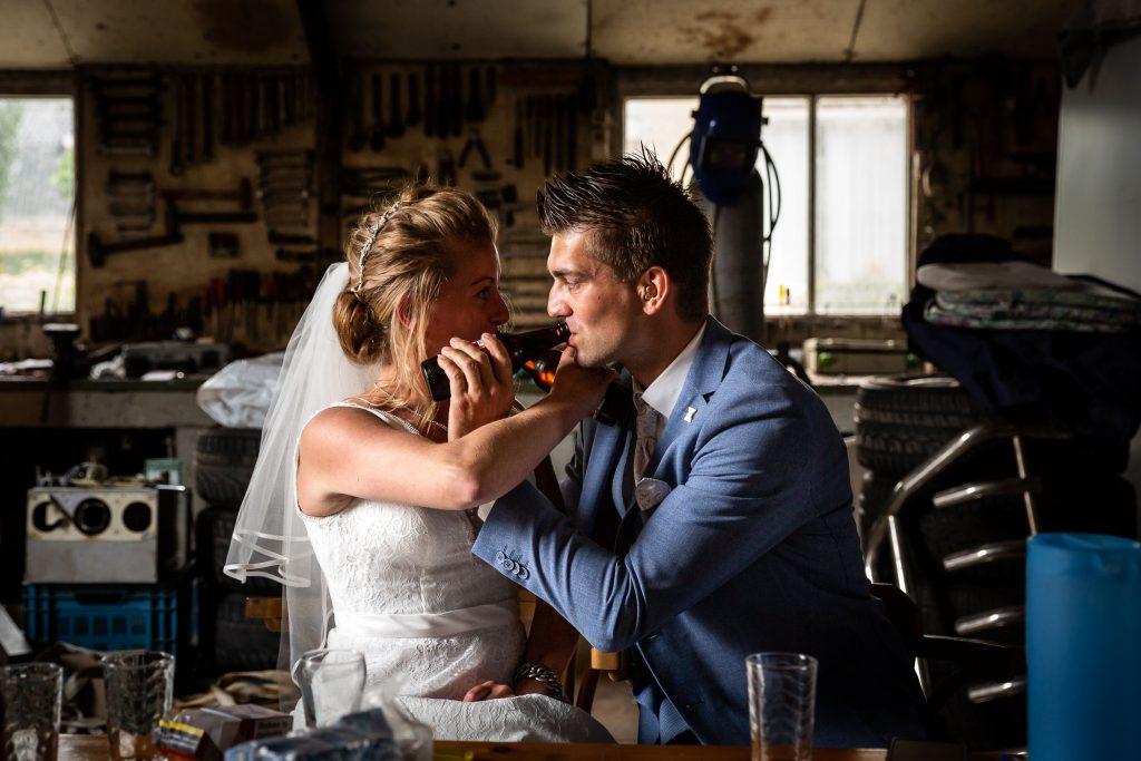 Bruidspaar proost samen op hun trouwdag en nemen de eerste slok van hun Amstel biertje in de schuur van het ouderlijk huis in west Friesland