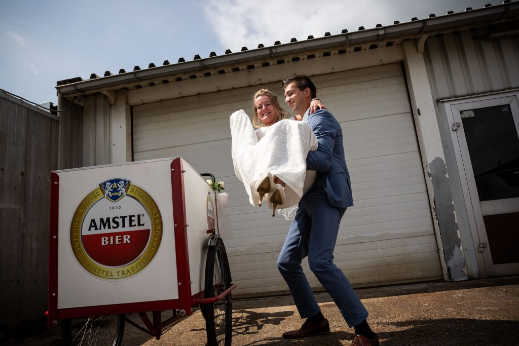 Bruidsfotografie Noord Holland trouwen in Spanbroek in 't Kerkhuys met trouwvervoer een Amstel bakfiets bruid wordt erin getild