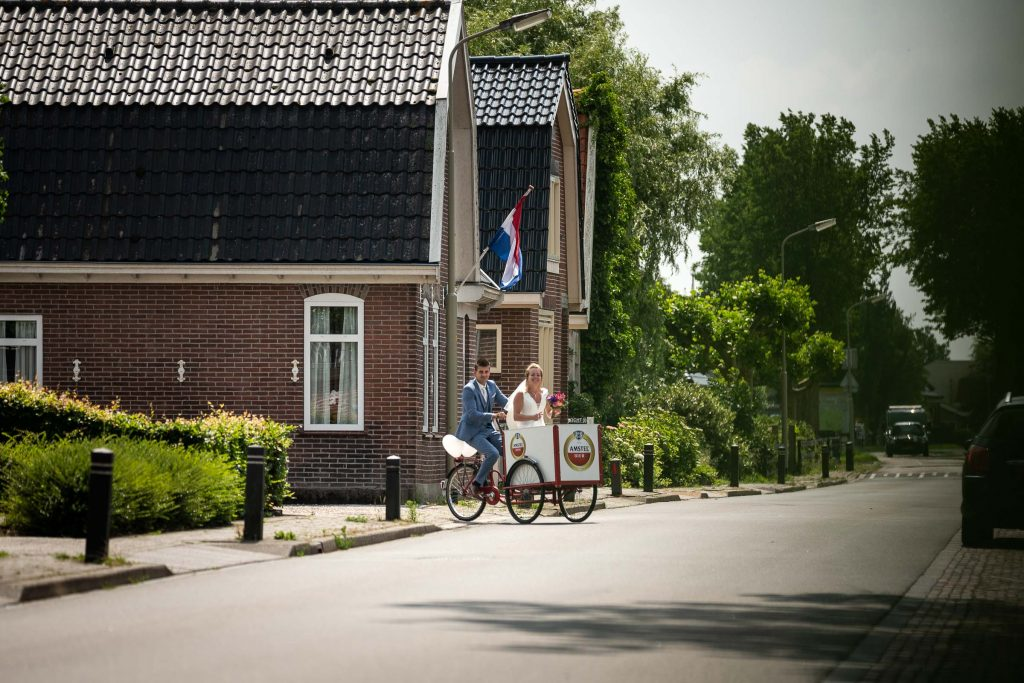 Bruidspaar vertrekt met de Amstel bakfiets naar de trouwlocatie in spanbroek een dorp vlakbij hoorn