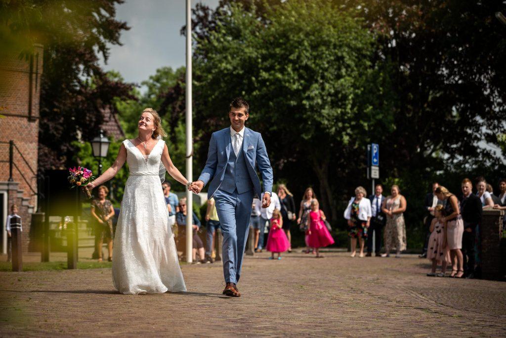 Bruidspaar loopt naar de kerk waar zij zullen trouwen met op de achtergrond alle daggasten van hun bruiloft