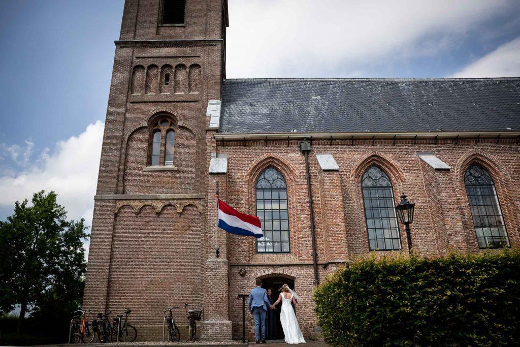 Bruidspaar loopt kerk binnen waar zij zullen trouwen, 't kerkhuis in spanbroek de ambtenaar wacht hen op