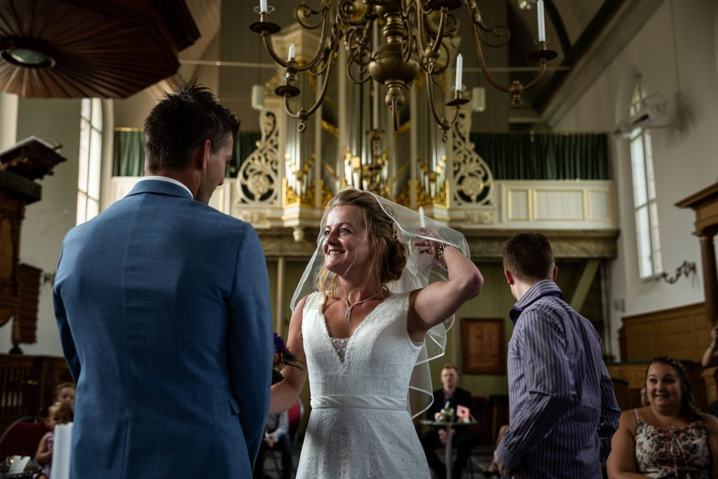 Bruid wordt weggegeven door haar broer en doet haar sluier af tijdens het begin van de trouwceremonie in de kerk