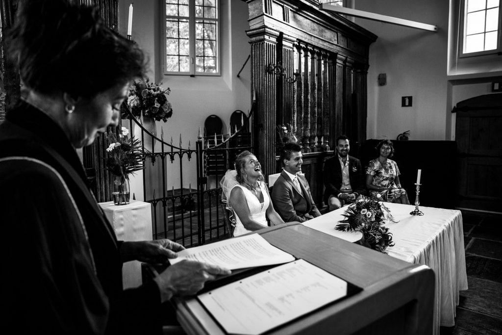 Tijdens het woordje van de ambtenaar van de burgerlijke stand wordt er flink gelachen door de bruid tijdens de trouwceremonie