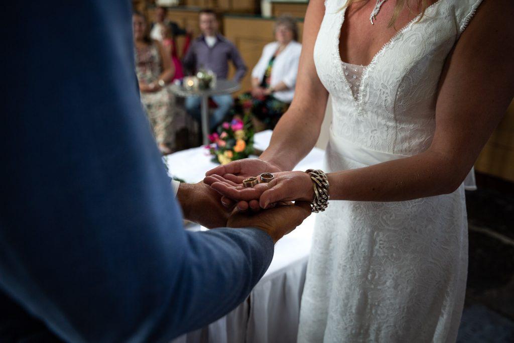 Bruidspaar hebben elkaars handen bij elkaar met de trouwringen op hun handen tijdens de trouwceremonie in de kerk van spanbroek