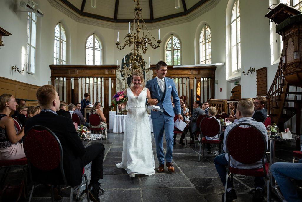 Just Married! Kersvers getrouwd bruidspaar loopt de kerkzaal uit onder applaus van familie en vrienden