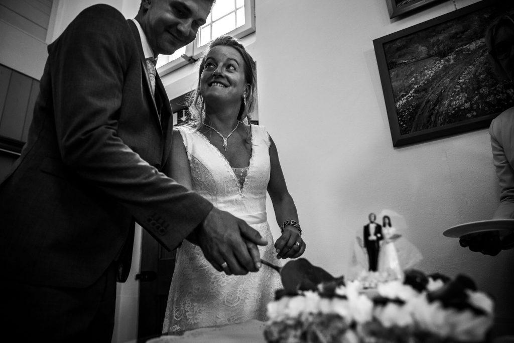 Bruidspaar snijd samen de bruidstaart aan na hun huwelijksceremonie