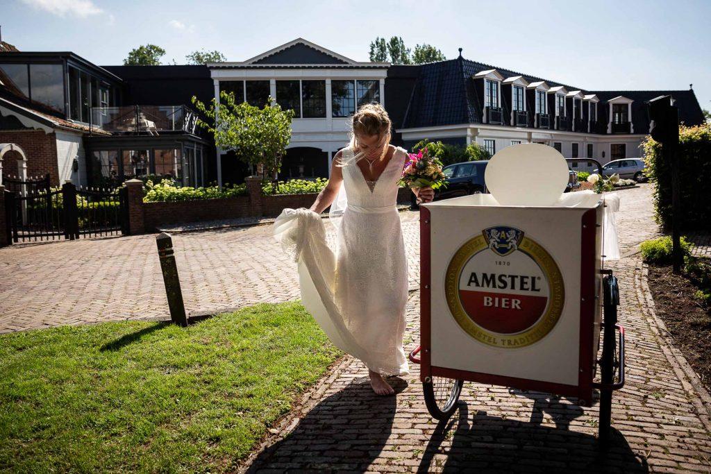 Bruid op blote voeten naast de Amstel bakfiets, hun trouwvervoer