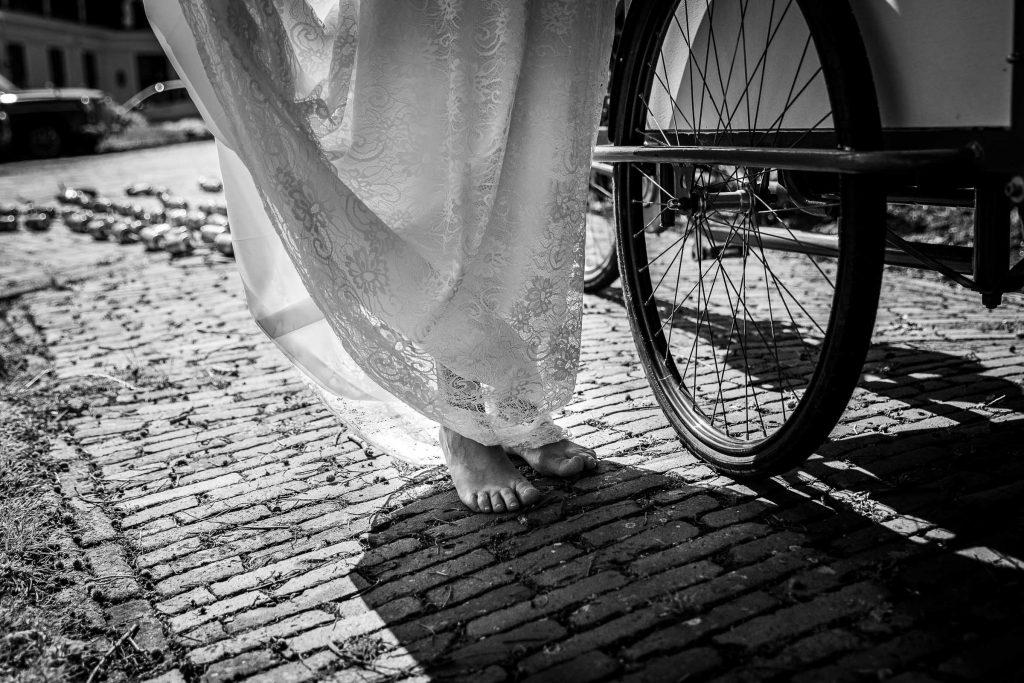Bruid op blote voeten naast het wiel van hun Amstel bakfiets tijdens de zomerbruiloft
