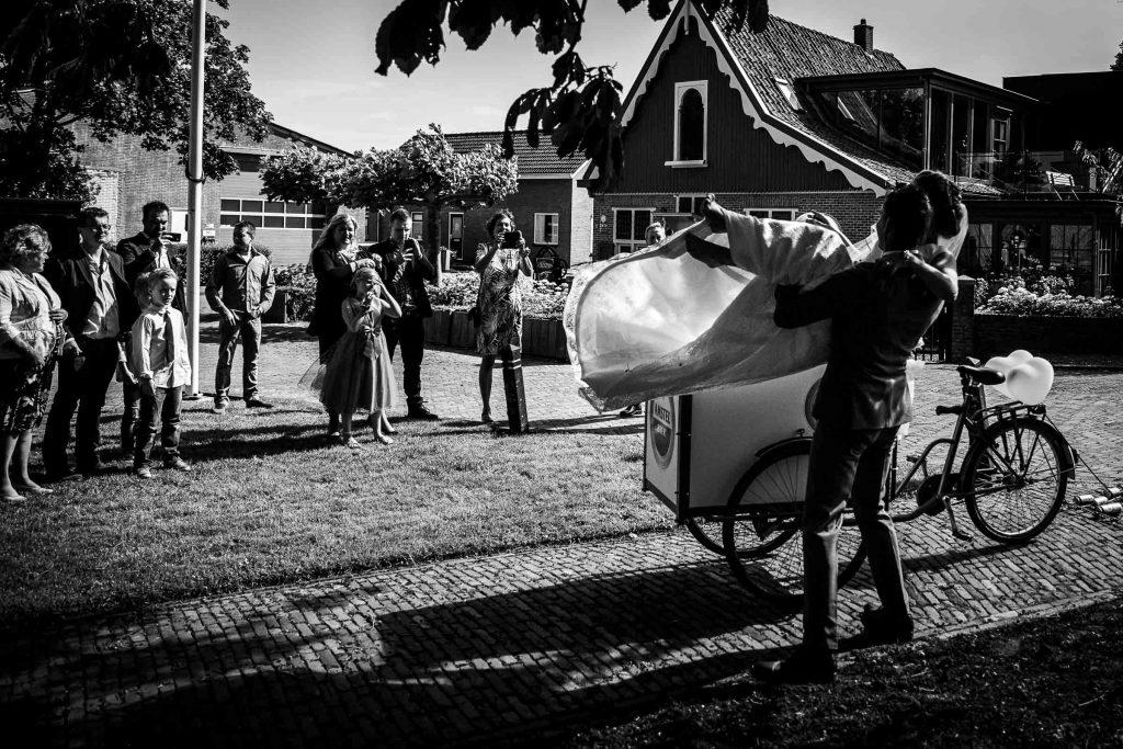 Bruid wordt in bakfiets getild en familie maakt daar foto's van op het kerkplein tijdens de zomerse bruiloft