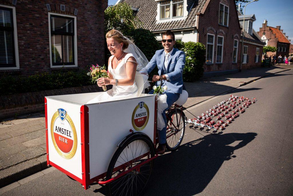 Just Married! Pas getrouwd en op de Amstel bakfiets onderweg van spanbroek naar Obdam met lawaai van de blikjes achter de fiets een zonnige bruiloft