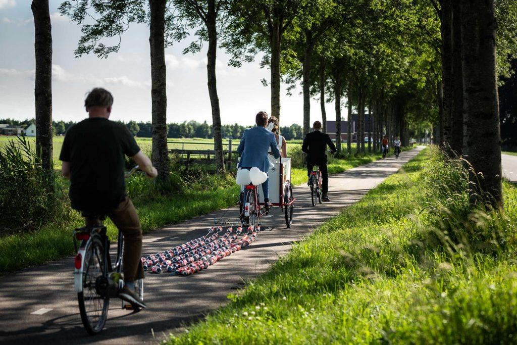 Bruidspaar is onderweg door een noord Hollands landschap met de bakfiets en blikjes daarachter tijdens een zonnige zomerse bruiloft