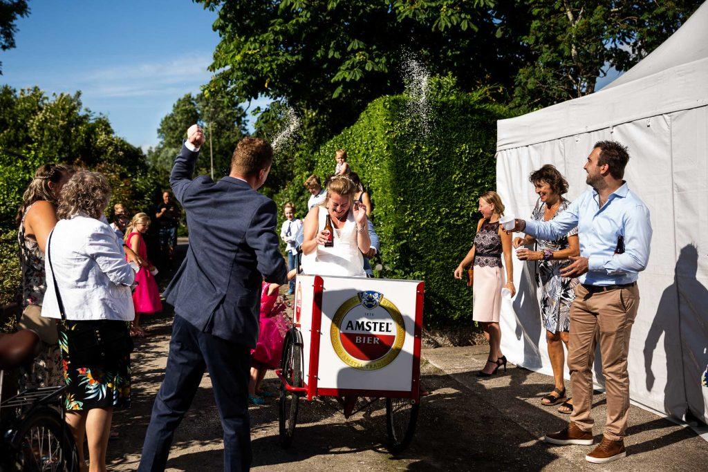 Bruidspaar wordt thuis ontvangen en bekogeld met rijst door familie en vrienden op hun zonnige bruiloft