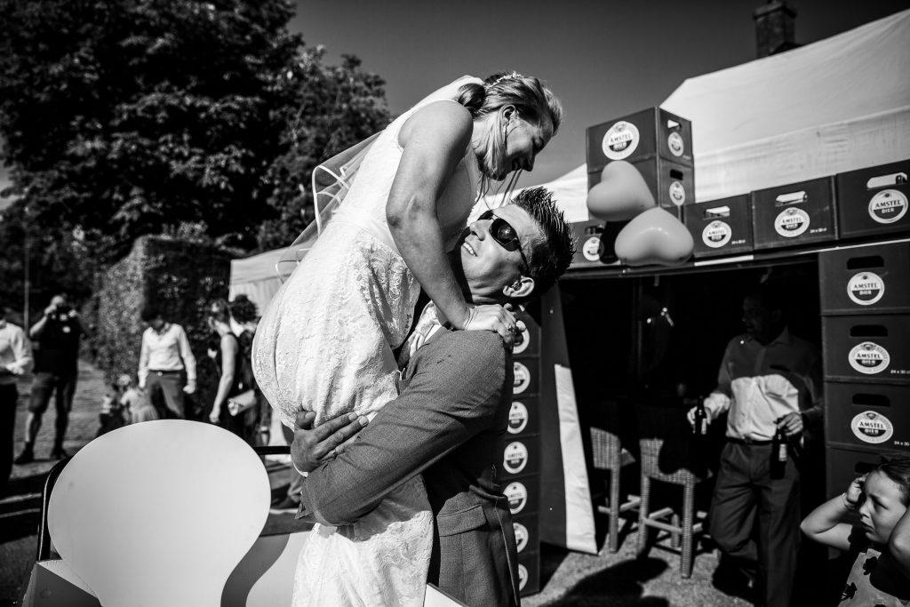 Bruidegom tilt bruid op uit de bakfiets op hun zonnige trouwdag in Obdam