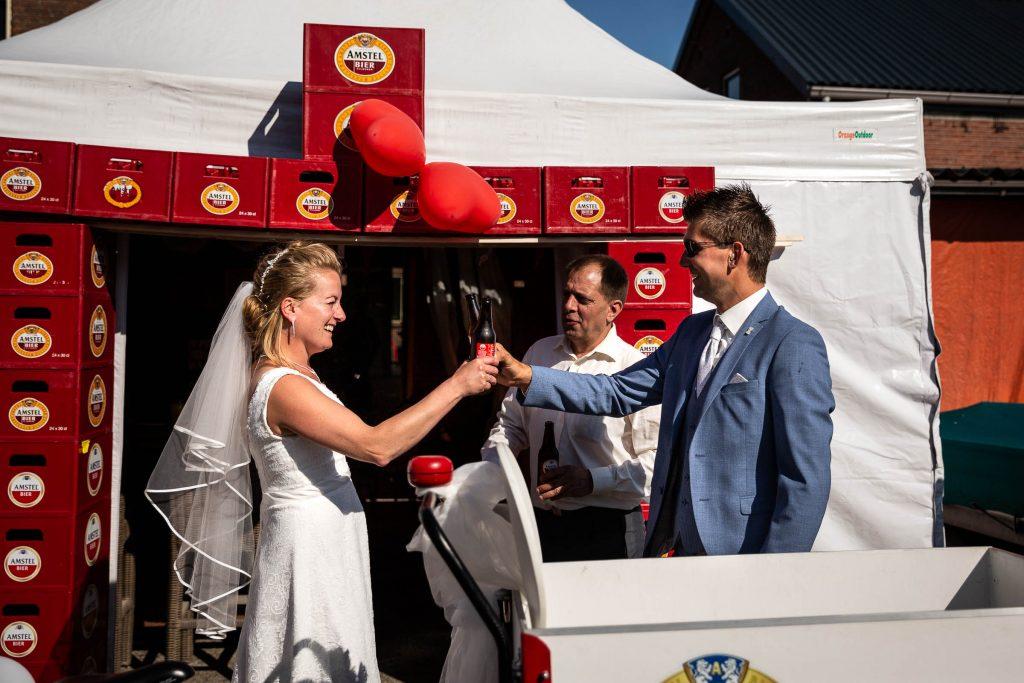Pas getrouwd bruidspaar proost samen met een Amstel biertje voor hun feesttent op hun huwelijk tijdens hun zonnige trouwdag in Obdam