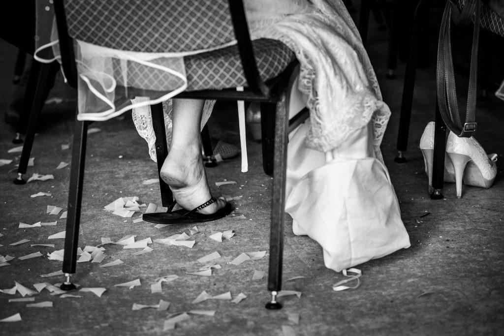 Bruidspaar draagt slippers aan 't einde van de trouwdag, trouwschoenen staan ernaast op hun trouwfeest in Obdam noord Holland
