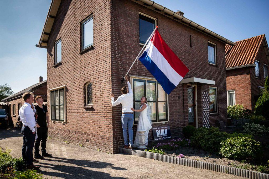 Bruidspaar hangt vlag uit op hun huis nadat ze zojuist zijn getrouwd op een zonnige zomerdag in juni