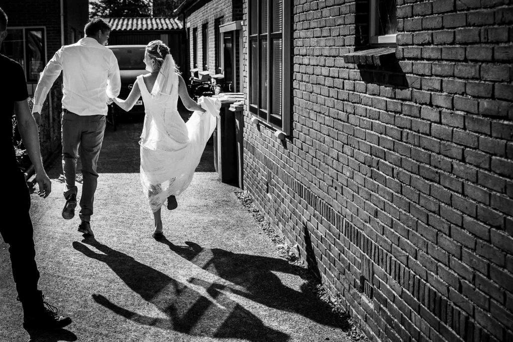 Het trouwgevoel een dolgelukkig bruidspaar huppelt hand in hand weg op de mooiste dag van hun leven
