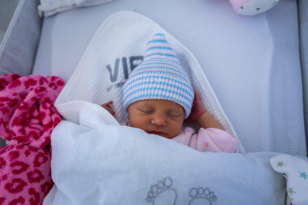 Pasgeboren baby ligt lief te slapen in haar eigen wiegje.