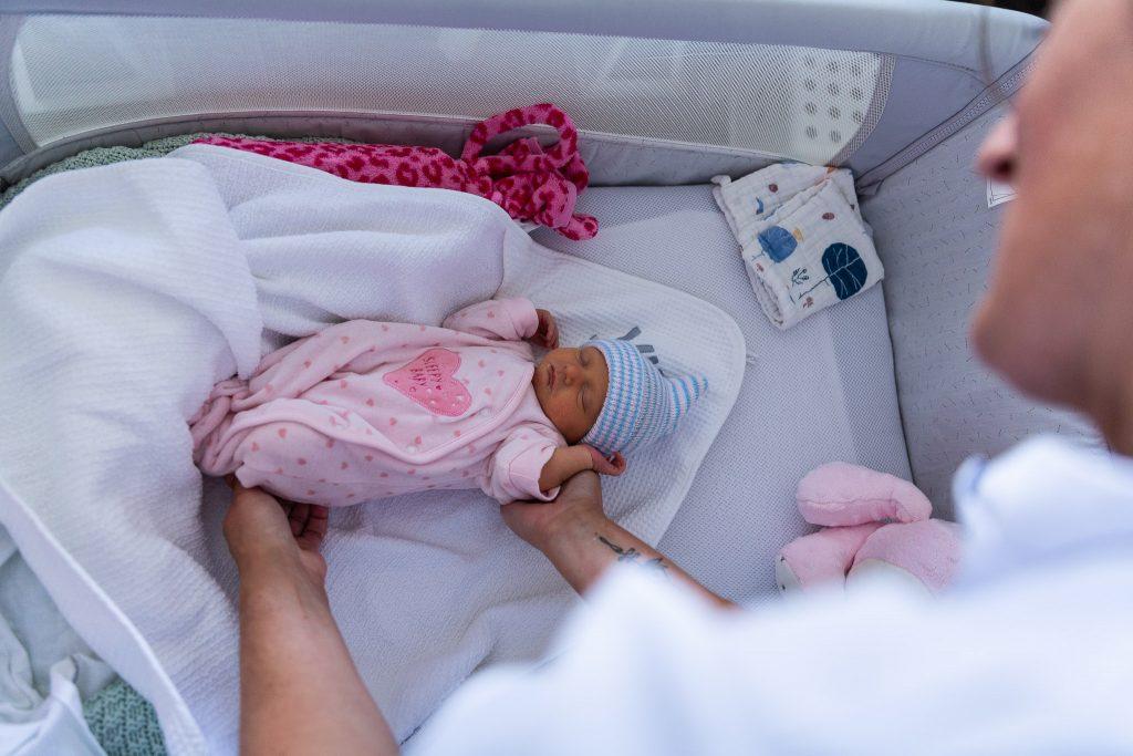 Kraamverzorgende pakt pasgeboren meisje op om te wegen en aan te kleden