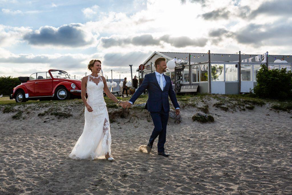 Bruidspaar loopt het strand op naar de ceremonie waar de gasten al op hun wachten