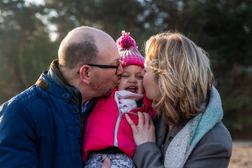 Dikke kussen van papa en mama tijdens een ongedwongen fotoshoot omdat mama zwanger is en je een zusje krijgt