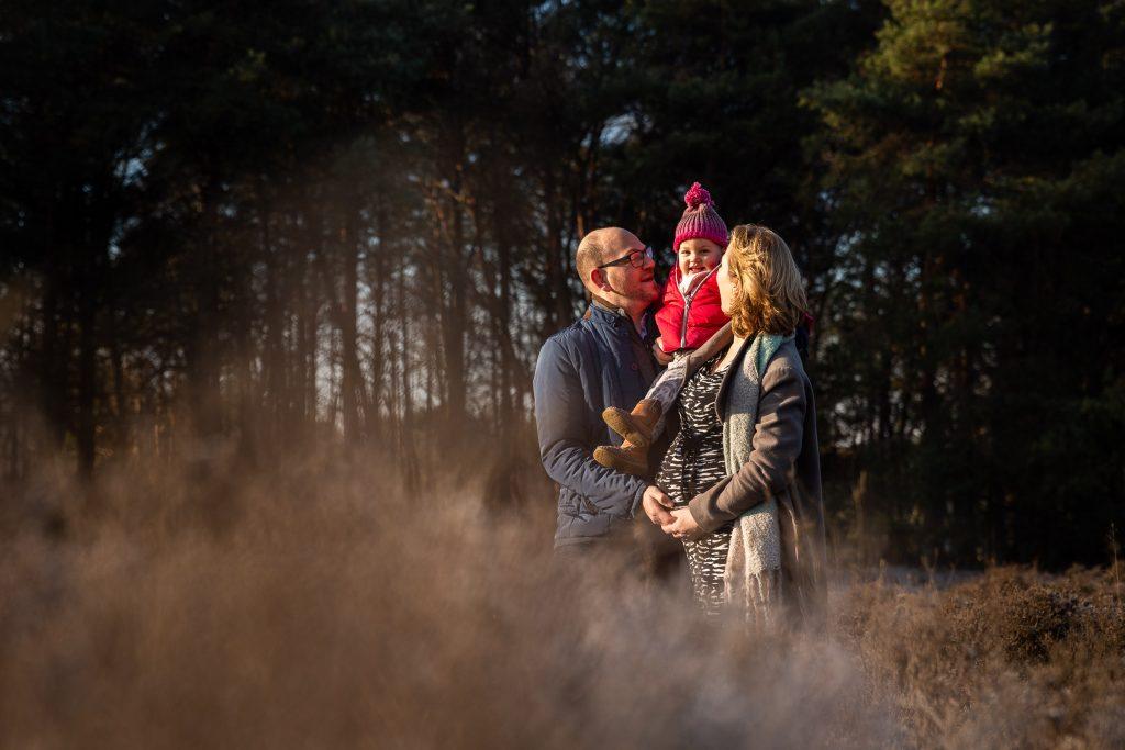 Het prachtige ochtendlicht op een mooie koude zondagochtend op de heide valt op een meisje die in de armen van haar ouders zit tijdens de zwangerschapsshoot
