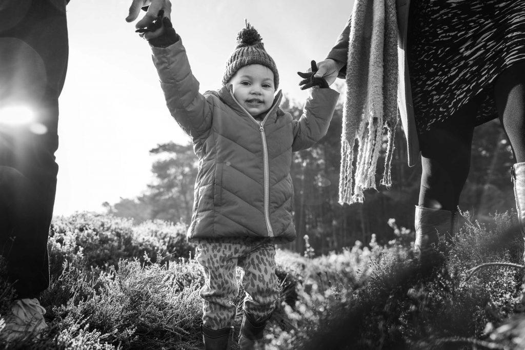 Portretfoto in zwart wit van een meisje die hand in hand loopt met haar ouders over de heide van Bussum tijdens een zwangerschapsfotoshoot bij de familiefotograaf