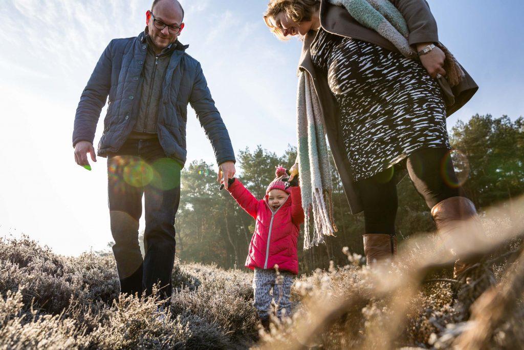 Pret maken samen met je ouders terwijl jullie over de heide lopen op een koude, frisse zondagochtend in Januari tijdens de fotoshoot met het gezin