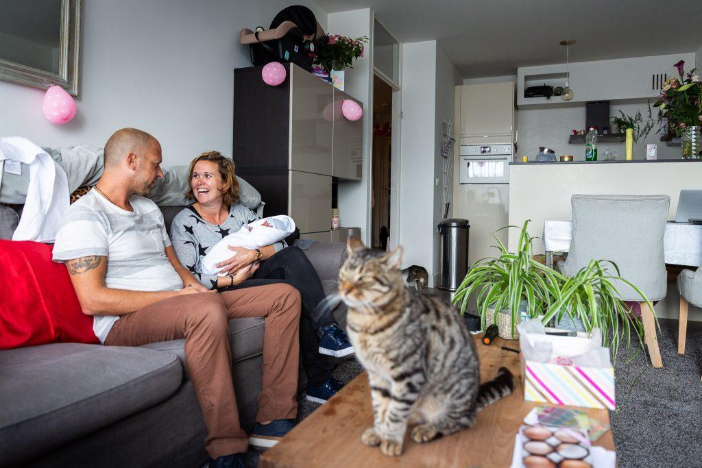 Vrienden maken kennis met de pasgeboren baby van hun vrienden terwijl de kat op de salontafel zit