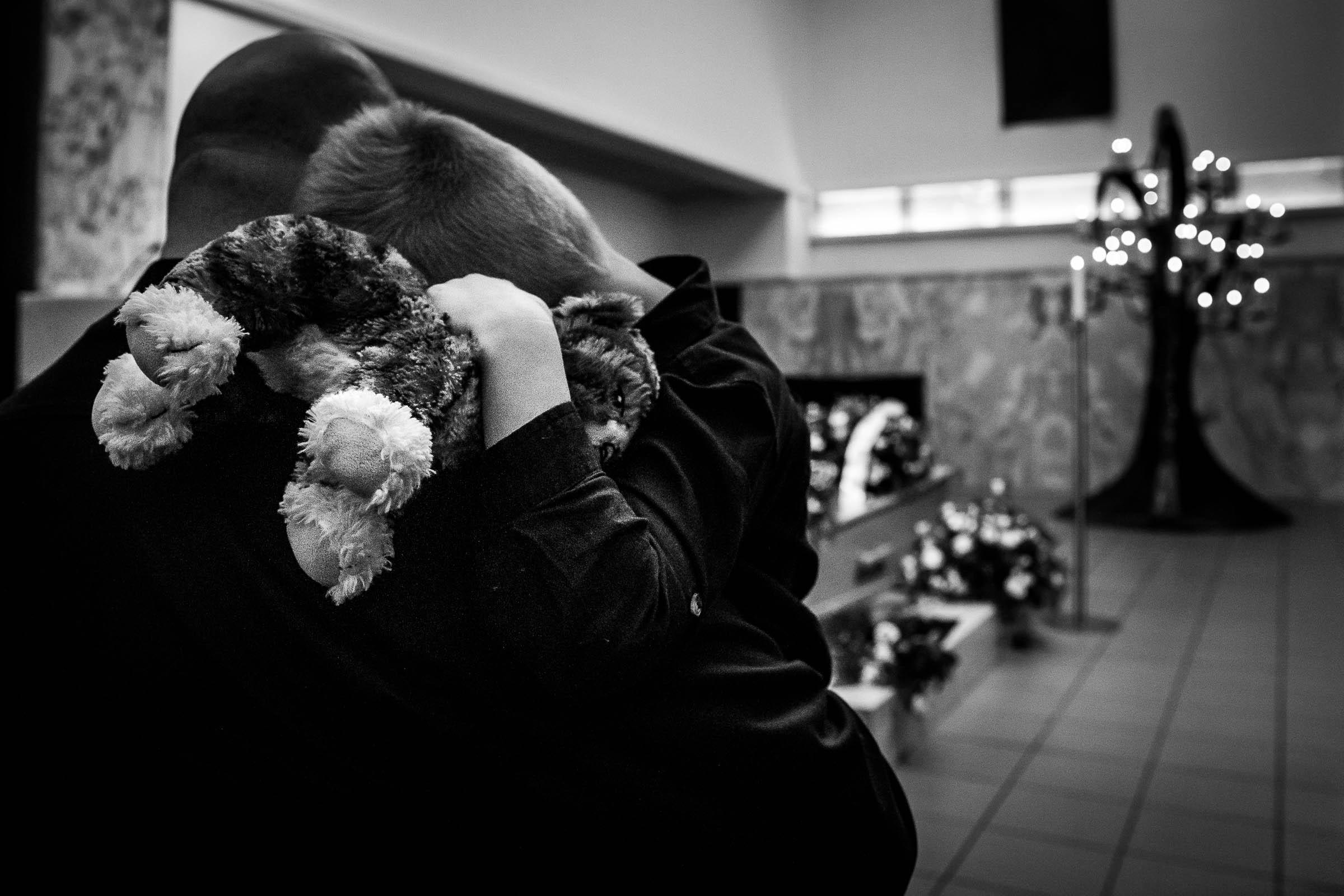 Jongen in de armen van zijn vader samen met zijn knuffel tijdens de uitvaart van zijn opa.