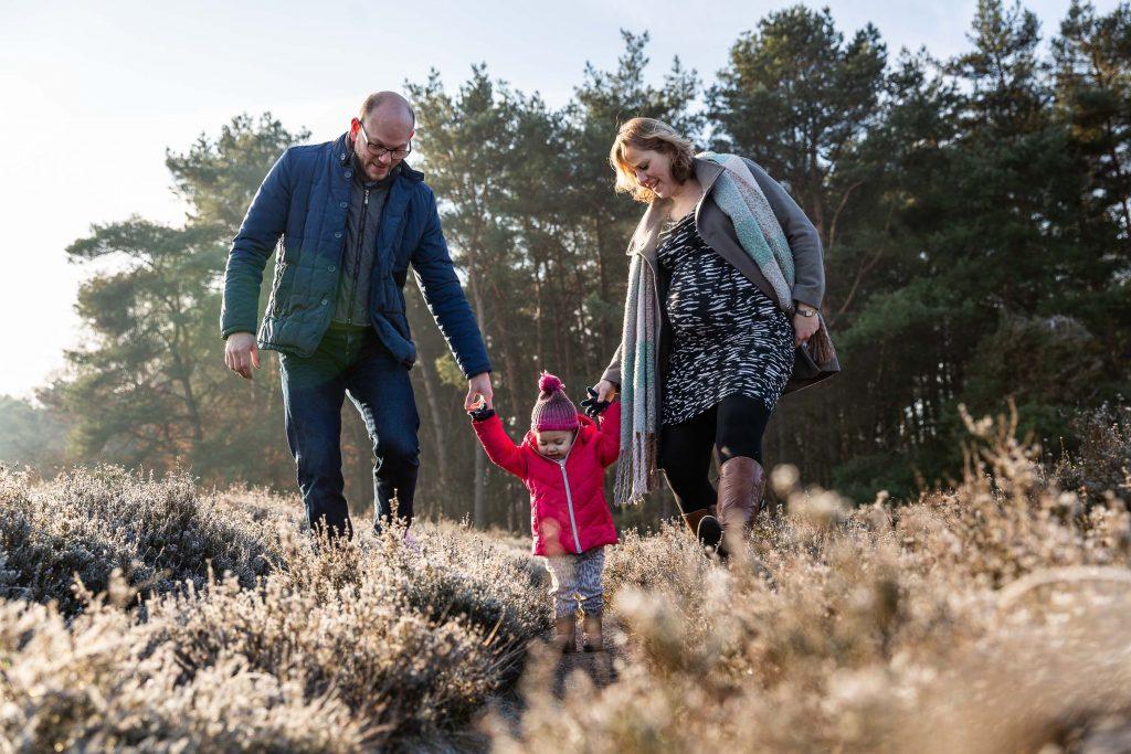 Hand in hand met je ouders over de heide tijdens de zwangerschapsfotoshoot bij de familiefotograaf