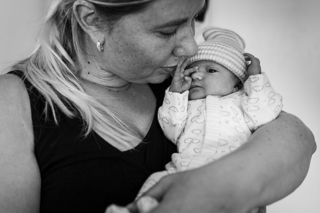 Moeder kust haar pasgeboren baby terwijl het meisje van vermoeidheid in haar ogen wrijft