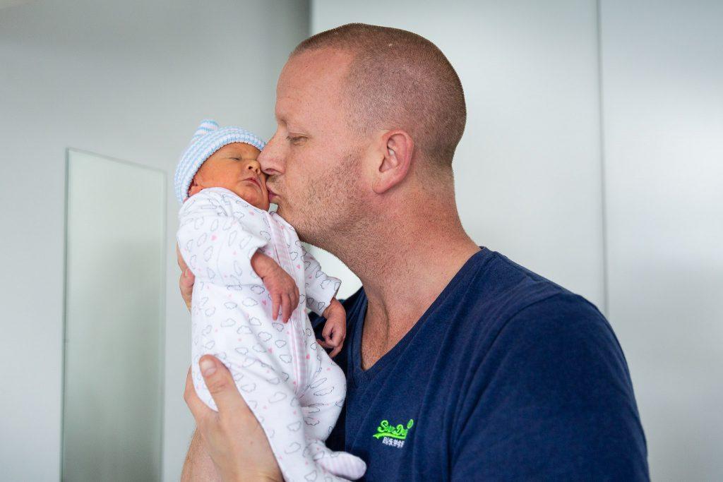 Vader geeft zijn pasgeboren dochter een liefdevolle kus op haar wang
