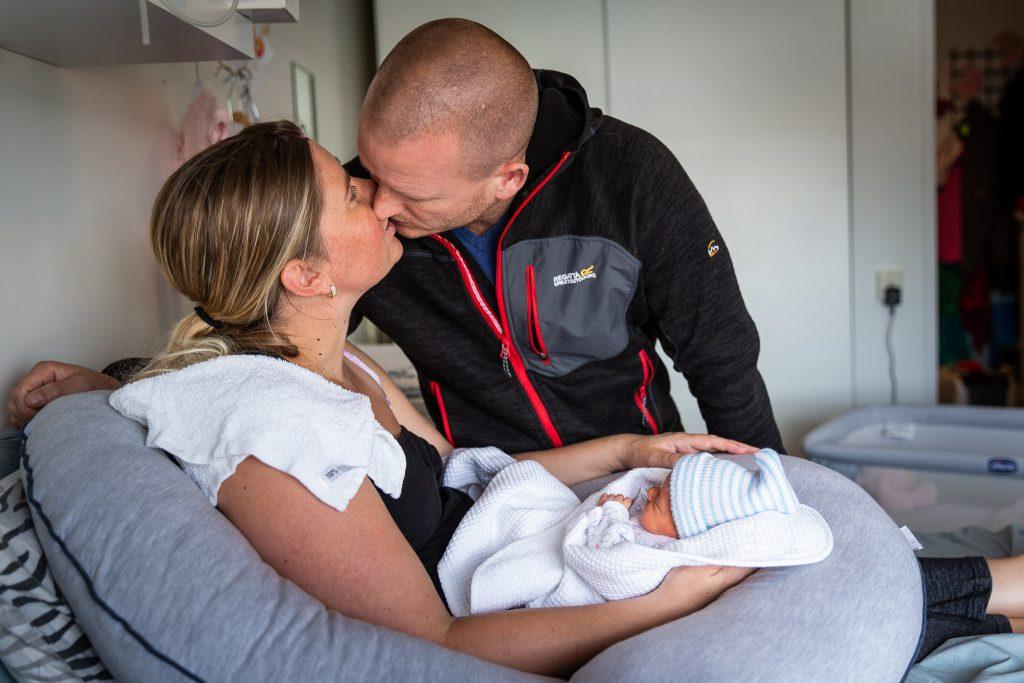 Man kust zijn vrouw terwijl hun pasgeboren kindje in de armen van de vrouw ligt